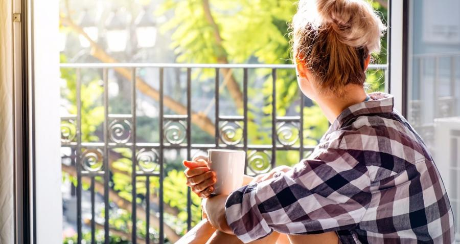 A young lady sits in the open balcony of her apartment with a cup of tea