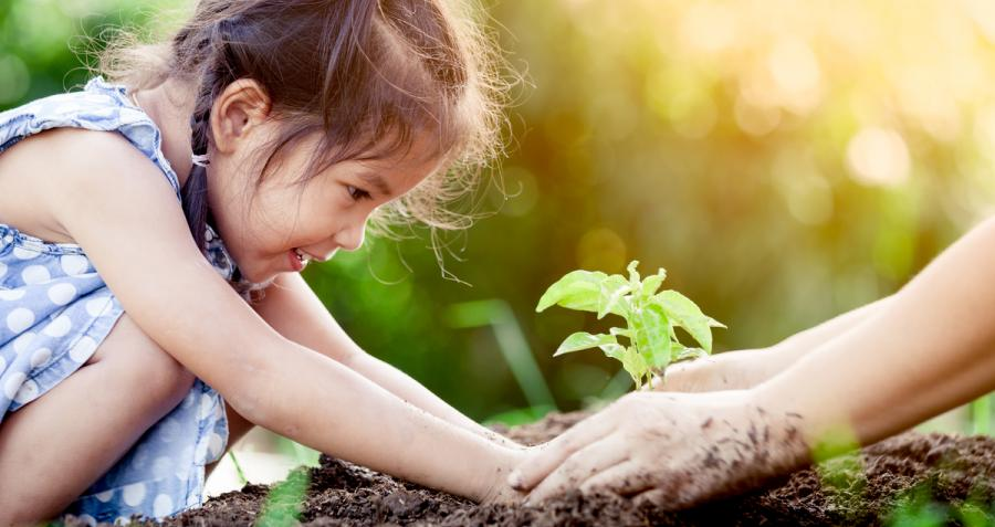 Child planting a plant outside with her mother