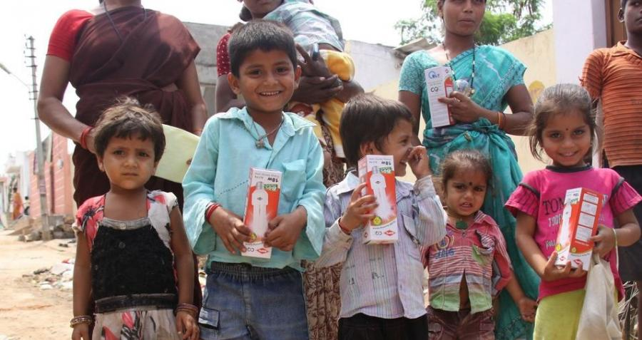Children in India holding compact fluorescent lighting (CFL) globes