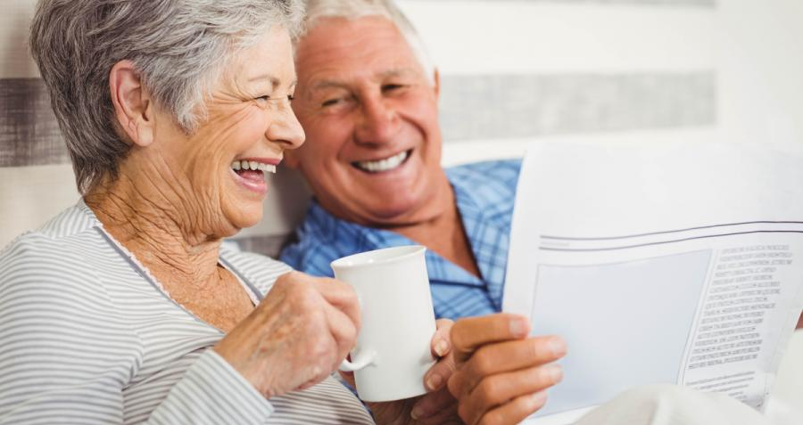Older couple laughing, drinking coffee and reading newspaper