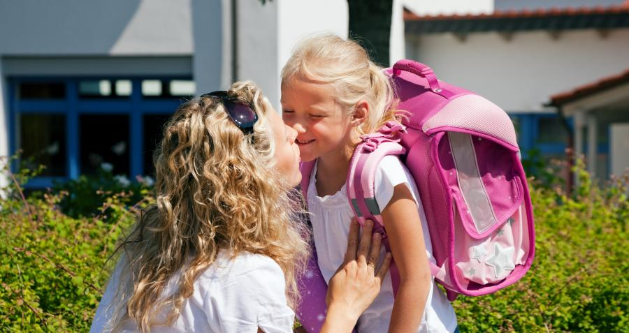 Mother kissing daughter goodbye as she goes to school
