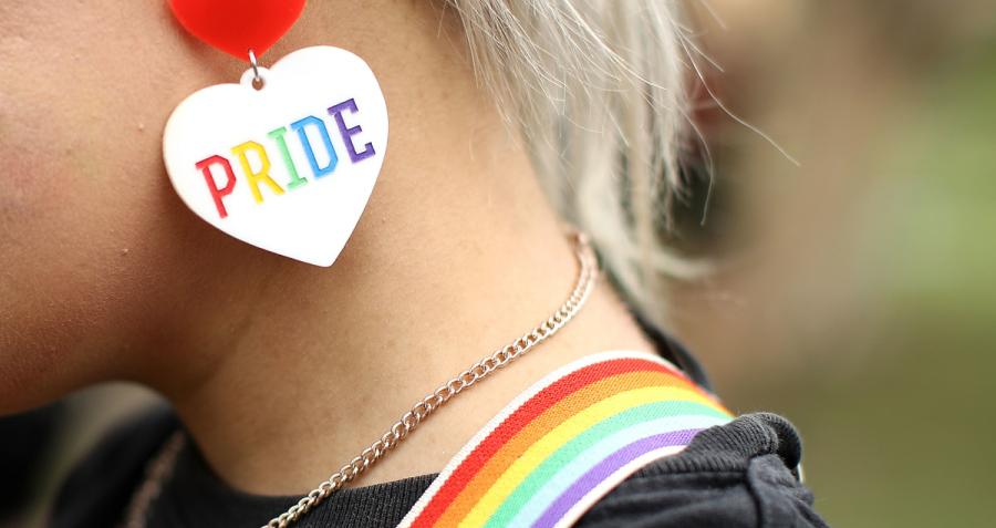 Woman with rainbow suspenders and pride earring