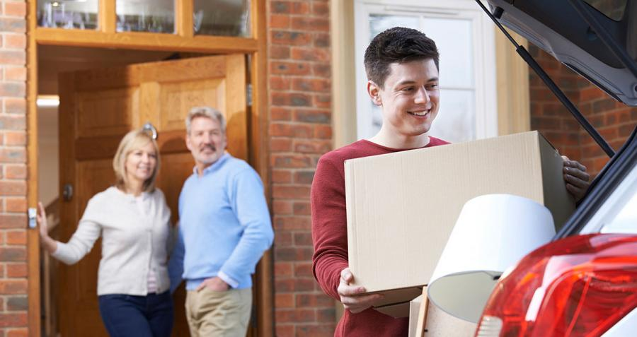 Young man moving out of home while proud parents look on