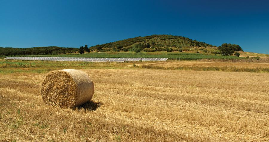 Country scene of hay bale in paddock with solar panels in background