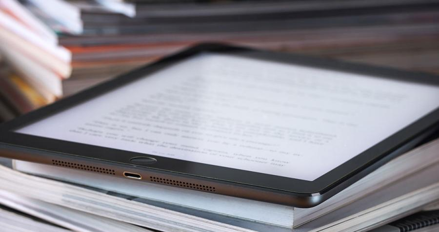 Tablet on pile of books with glasses