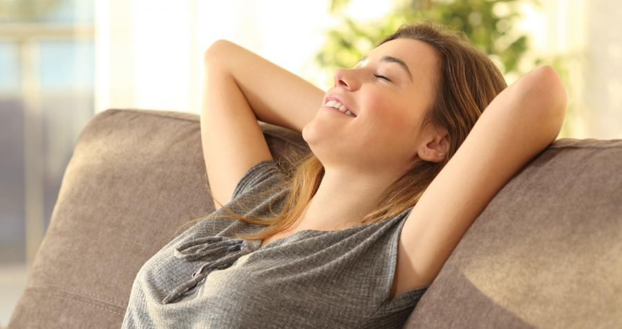 Smiling woman leaning back against couch
